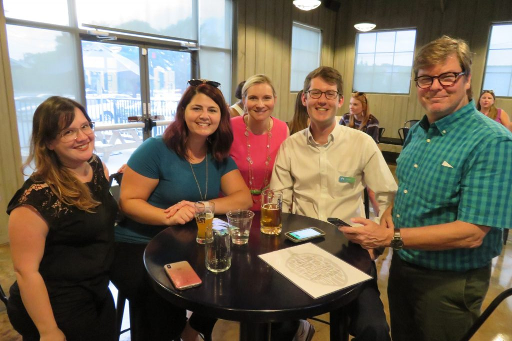 group smiling and enjoy beer at columbia craft brewery